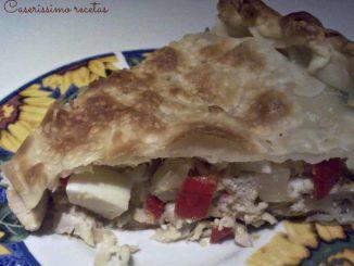 Se muestra una porción de tarta de pollo, huevo, morrón, cebolla y masa.